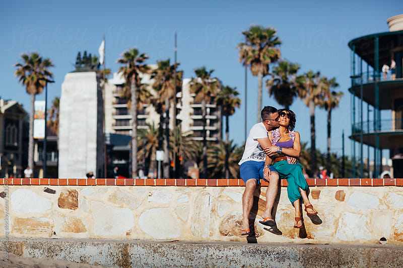 Young couple sit together on holiday sharing a passionate moment by Robert Lang for Stocksy United