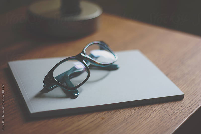 A pair of spectacles resting on a notebook by Helen Rushbrook for Stocksy United