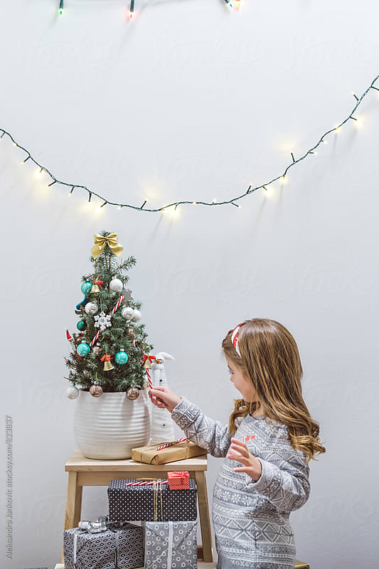 Little Girl Decorating Christmas Tree by Aleksandra Jankovic for Stocksy United