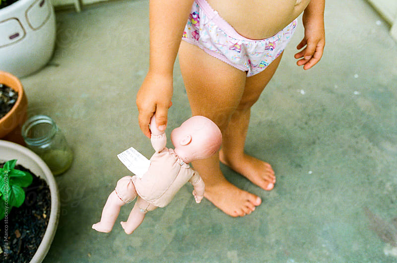 overhead view of little girl holding baby doll by Maria Manco for Stocksy United