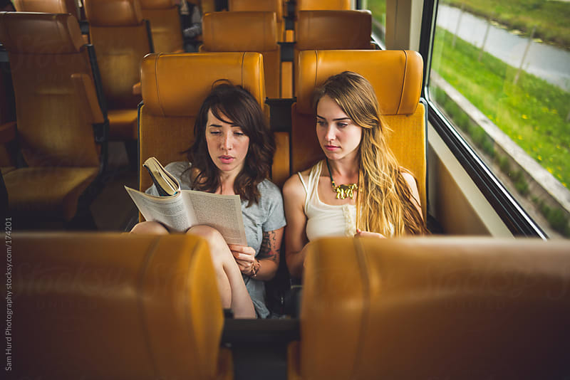 girls reading on a train by Sam Hurd Photography for Stocksy United
