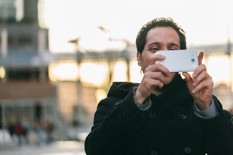 Young man taking a photo with your smartphone by Davide Illini for Stocksy United