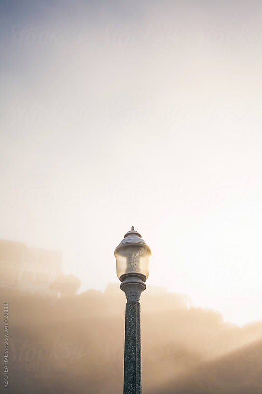 Light post with early morning sun through fog. by RZ CREATIVE for Stocksy United
