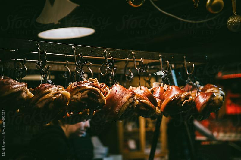 Pork knuckle hanging by Martí Sans for Stocksy United