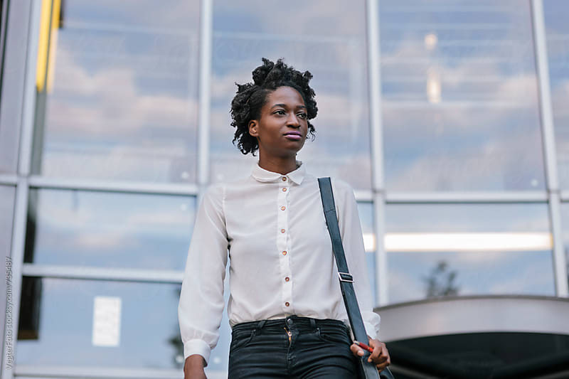 Black Woman leaving Office Building by VegterFoto for Stocksy United