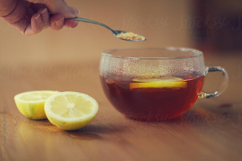 Hot tea in glass mug with lemon and sugar by Kerry Murphy for Stocksy United