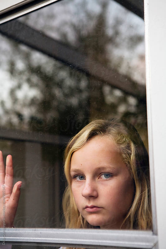Blonde Teenager Looking Through Window With Serious Expression by Dina Giangregorio for Stocksy United