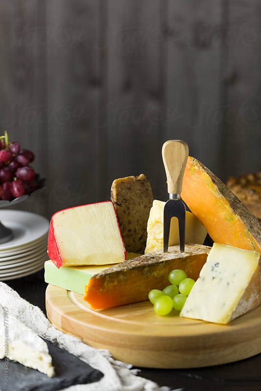 Vertical shot of cheese board with grapes by Kirsty Begg for Stocksy United