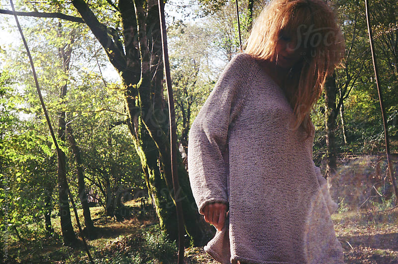 A film portrait of young beautiful redhead woman standing on suspension bridge by Anna Malgina for Stocksy United