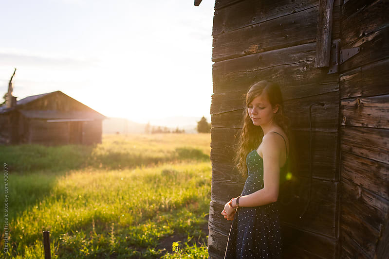 Young girl leaning on a barn with sunflare looking left by Christian Tisdale for Stocksy United
