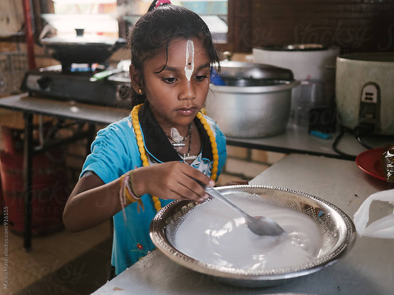 Indian girl stirring milk in bowl by Martin Matej for Stocksy United