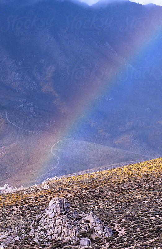 telephoto rainbow rocky hillside during rainstorm ridgecrest california desert arid steppe by Ron Mellott for Stocksy United