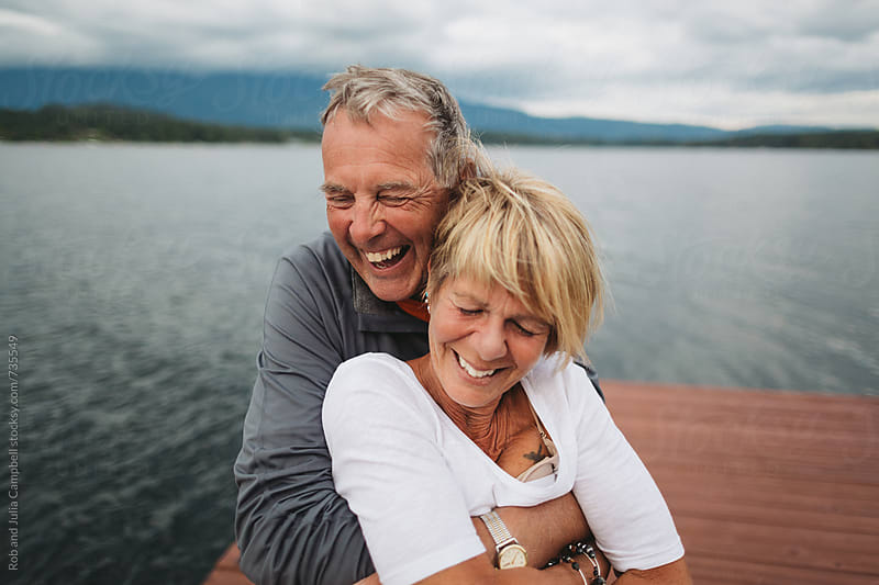Fun, mature couple fugging together on dock at the lake by Rob and Julia Campbell for Stocksy United