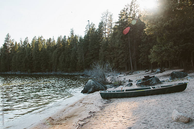 Green canoe resting on a sandy beach.  by Justin Mullet for Stocksy United