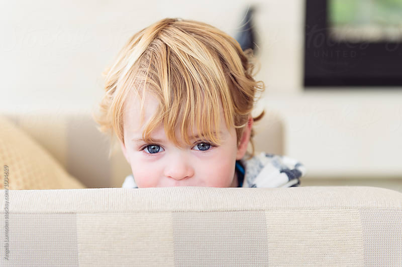 Cheeky toddler hiding behind furniture by Angela Lumsden for Stocksy United