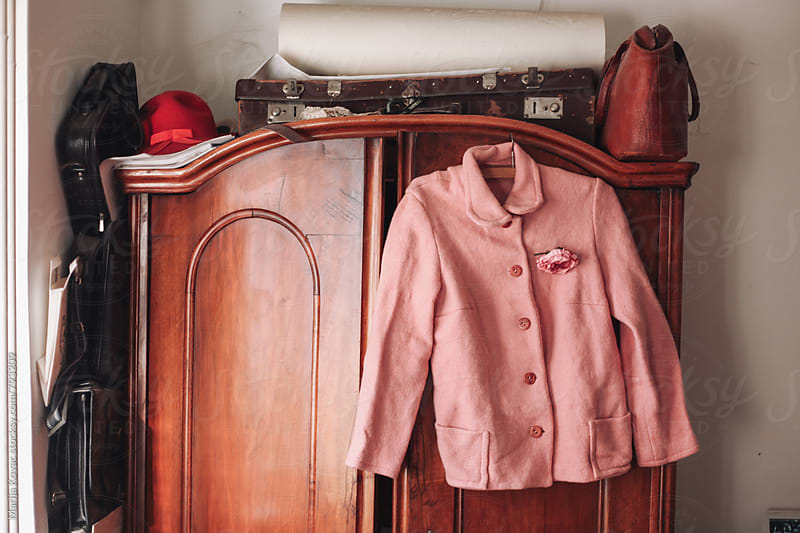 Pink jacket hanging on an old closet - horizontal by Marija Kovac for Stocksy United