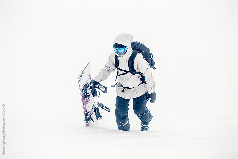 Female snowboarder walking in the snow with snowboard by Søren Egeberg Photography for Stocksy United
