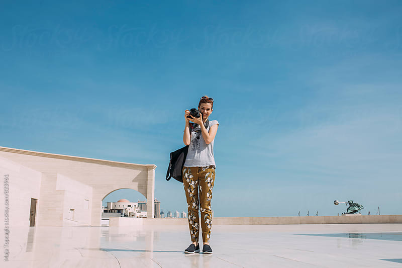 Young female photographer taking photos in the old town Katara by Maja Topcagic for Stocksy United