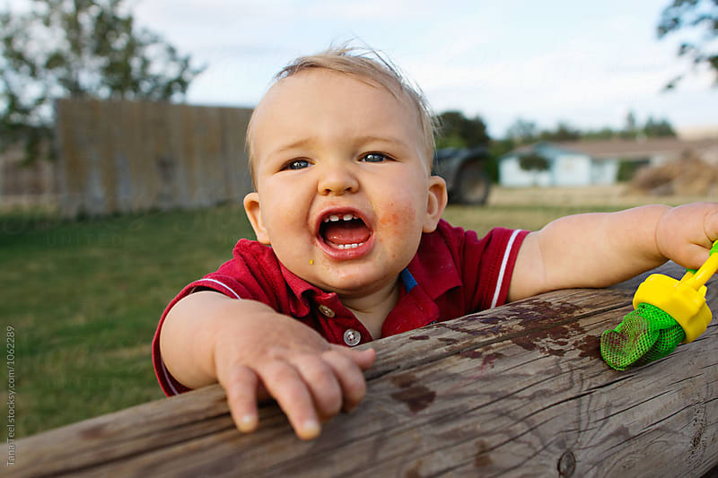 smiling toddler stands against fence outside by Tana Teel for Stocksy United