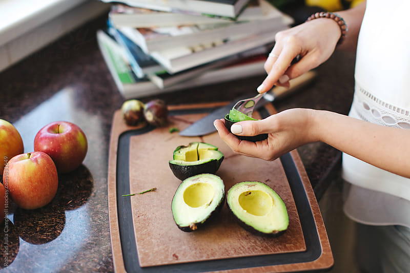 Young woman's hands in kitchen preparing food - slicing avocados by Rob and Julia Campbell for Stocksy United