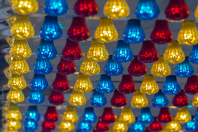 Red, yellow and blue fairground lights under a canopy by Paul Phillips for Stocksy United