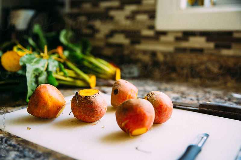 golden beets on a cutting board by Sarah Lalone for Stocksy United