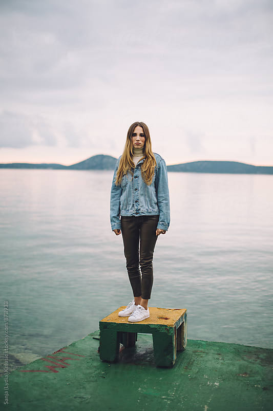 Young women dressed in 90's outfit standing alone by the sea by Sanja (Lydia) Kulusic for Stocksy United