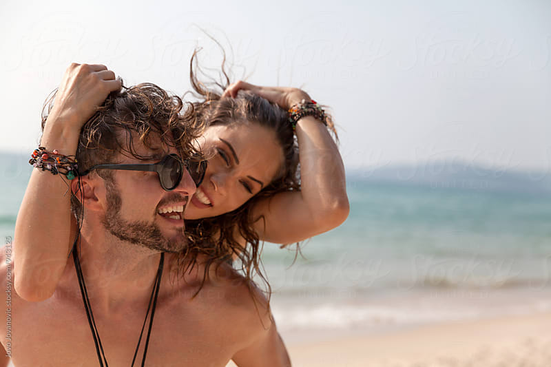 Couple in love laughing at the beach by Jovo Jovanovic for Stocksy United