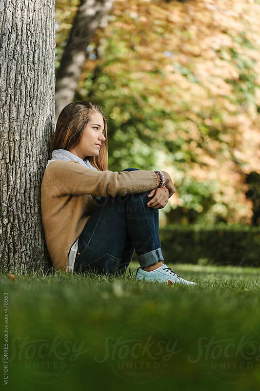 Teenage Girl Sitting Next to a Tree in the Park by VICTOR TORRES for Stocksy United