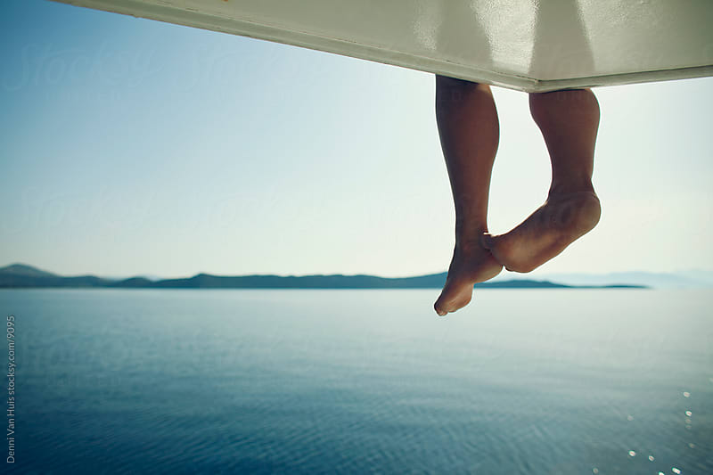 Dangling legs over the side of a boat by Denni Van Huis for Stocksy United