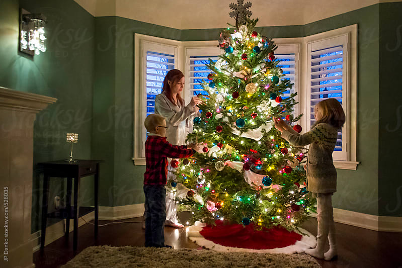 Mother Little Boy and Girl Decorating Family Christmas Tree by JP Danko for Stocksy United