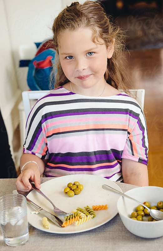 young girl at the dinner table by Andreas Gradin for Stocksy United
