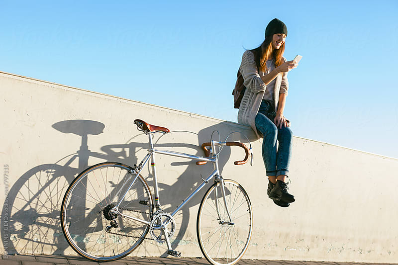 Woman with her vintage bicycle using her phone sitting outside. by BONNINSTUDIO for Stocksy United