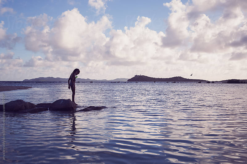 Girl standing on the water's edge in silhouette by anya brewley schultheiss for Stocksy United