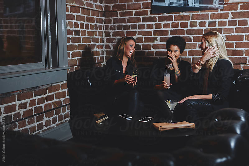 Group of ladies laughing while drinking by Alicja Colon for Stocksy United