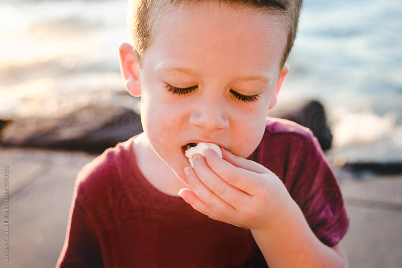 Little boy eating a marshmallow by the lake by Lindsay Crandall for Stocksy United