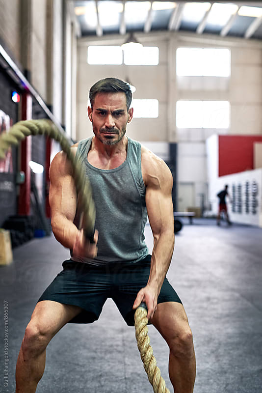 Man working out with exercise ropes in a gym by Guille Faingold for Stocksy United