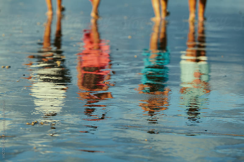 People Having a Walk in the Sea Shore Reflected on Water by VICTOR TORRES for Stocksy United