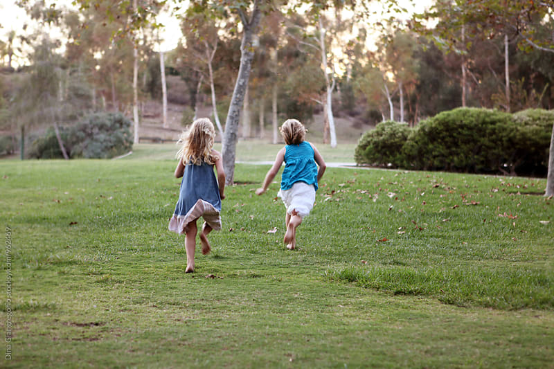 Two Girls From Behind Running In Park by Dina Giangregorio for Stocksy United