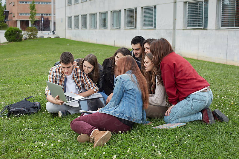 Group of students watching a video in university campus by Miquel Llonch for Stocksy United