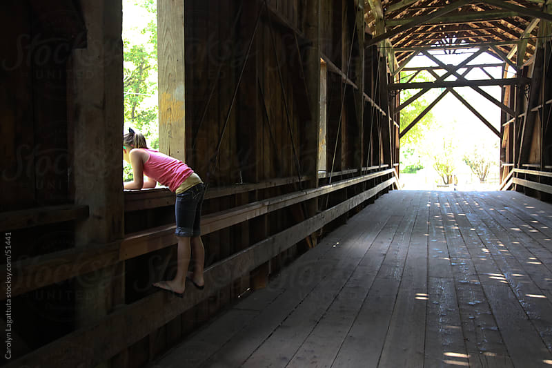 Girl inside a covered bridge, looking out over the water. by Carolyn Lagattuta for Stocksy United