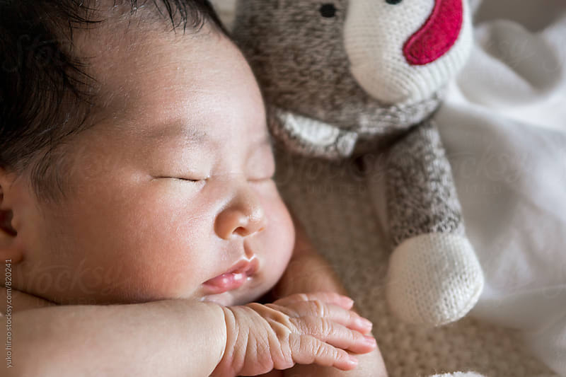 Close up of an Asian newborn baby, sleeping by yuko hirao for Stocksy United