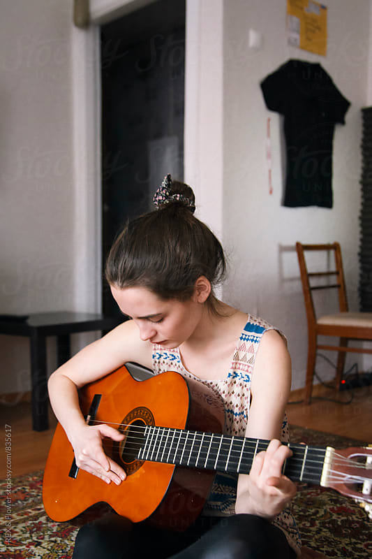 Close-up of young woman playing the guitar by Danil Nevsky for Stocksy United