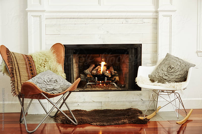Modern chairs in front of fireplace in living room by Trinette Reed for Stocksy United