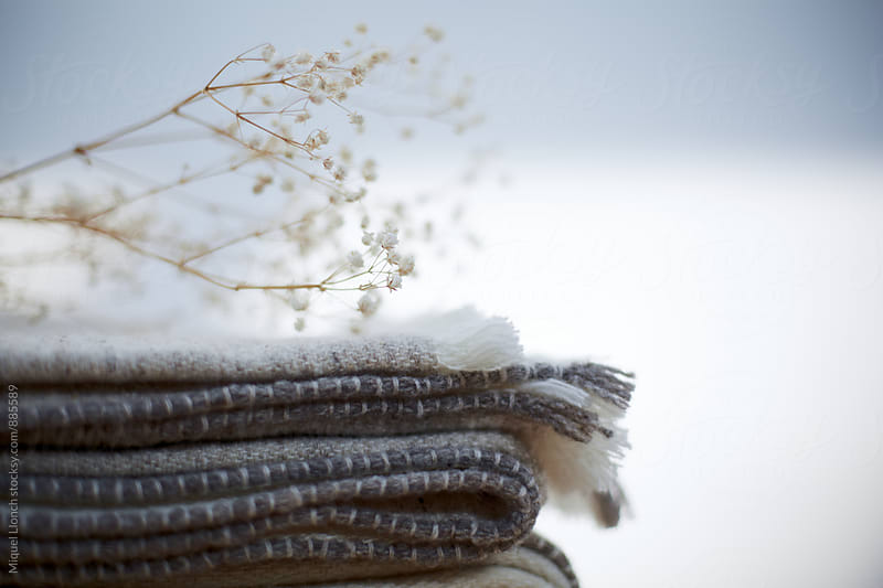 Stack of blankets with dry flower by Miquel Llonch for Stocksy United