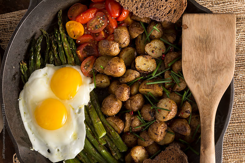 Breakfast:  Fried Eggs on Grilled Asparagus, Potatoes and Cherry Tomatoes by Jeff Wasserman for Stocksy United