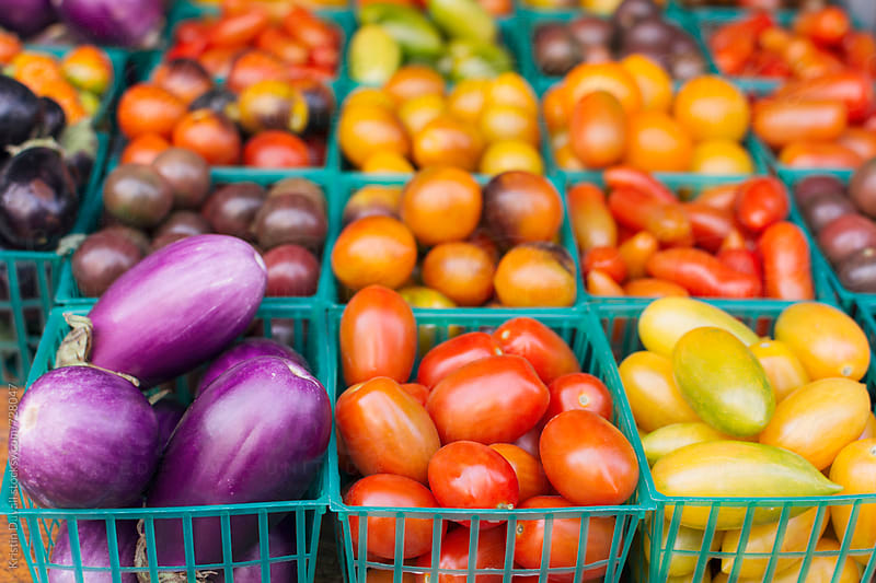 Fresh tomatoes and eggplants at market by Kristin Duvall for Stocksy United