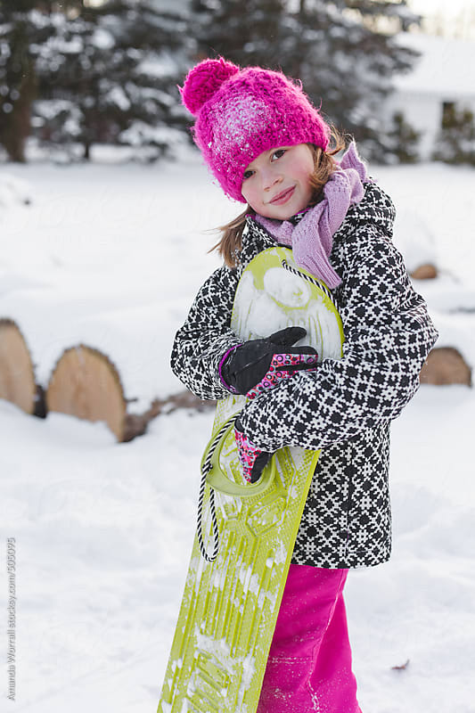 Young girl sweetly hugging her snowboard by Amanda Worrall for Stocksy United