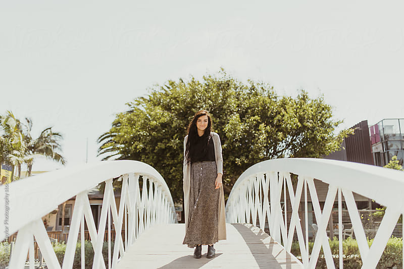 Young woman on bridge by Isaiah & Taylor Photography for Stocksy United