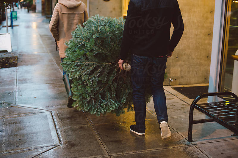 Couple crossing downtown street with Christmas tree at dusk. by Kate Daigneault for Stocksy United